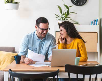 couple sitting at computer to pay bills together