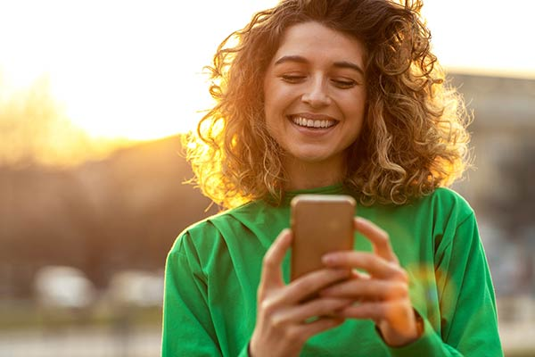 woman smiling as she checks her account balance on her phone