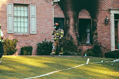 firefighter inspecting a burned home