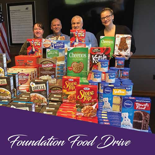 employees posing with food drive items