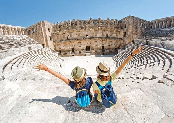 2 travelers sightseeing at the colusseum in rome