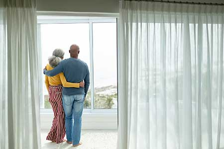 couple in their 60s looking out from their picture window